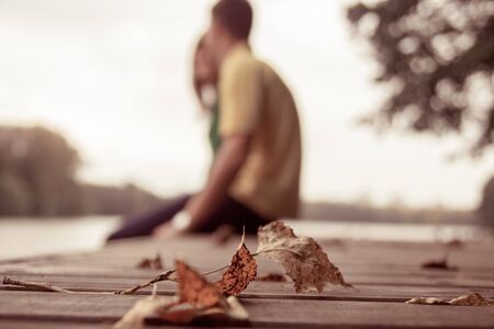 Autumn leaf lying in the park with a couple on the background 写真素材