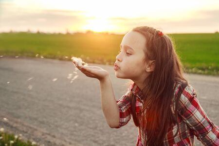 blows: girl blows on a dandelion