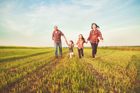 family running together in the field Stock Photo