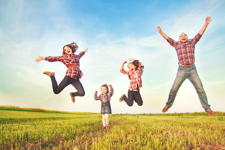 family on grass: family jumping together in the field
