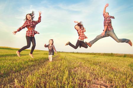 family jumping together in the field