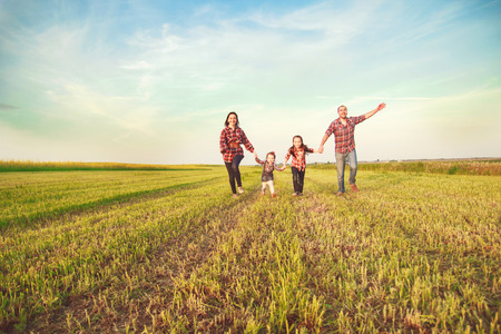 family running together in the field 写真素材