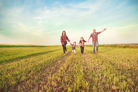happy family: familia corriendo juntos en el campo Foto de archivo