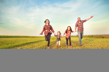 man field: family running together in the field Stock Photo