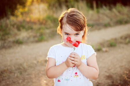 little girl with a flower in the hands Stock Photo