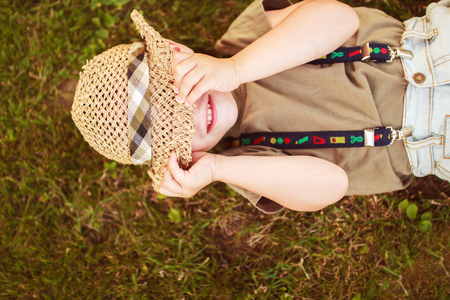 suo: boy hiding his face with his hat and smiling