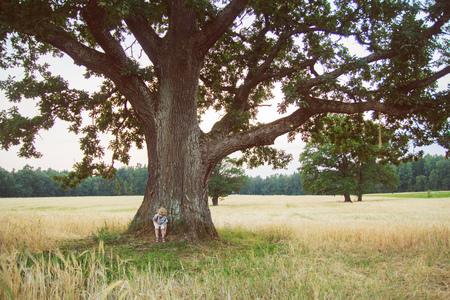 near: kid stands near a tree