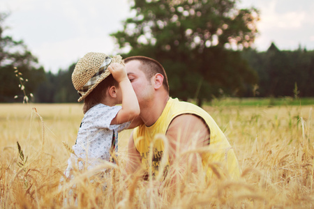 kiss love: boy kiss his father in the field Stock Photo