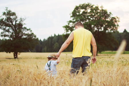 road shoulder: man walking with his kid in the field Stock Photo