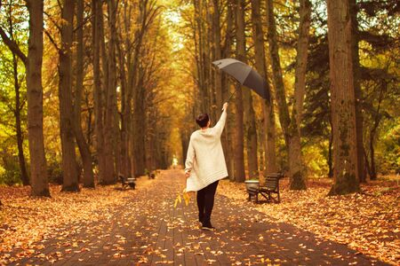 rain: girl with an umbrella in the park
