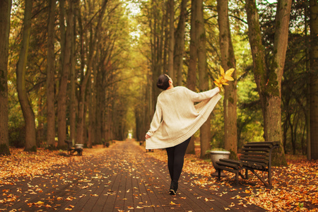 girl walking in the park in autumn