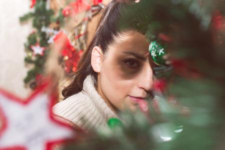 peeping: Girl peeping from behind Christmas tree Stock Photo