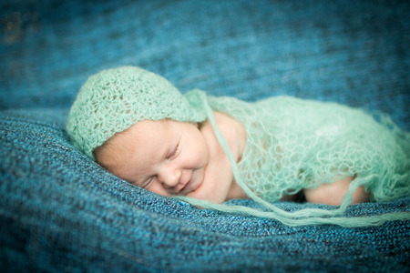 sweetly: newborn baby sleeping sweetly on a blue rug in blue cap Stock Photo