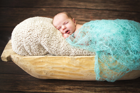 trough: Newborn baby sleeping on a wooden background in the trough