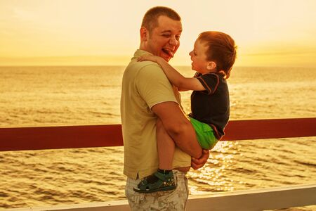 piddle: Dad and son playing at the pier on the sea at sunset Stock Photo