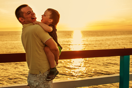 Dad and son playing at the pier on the sea at sunset Stock Photo