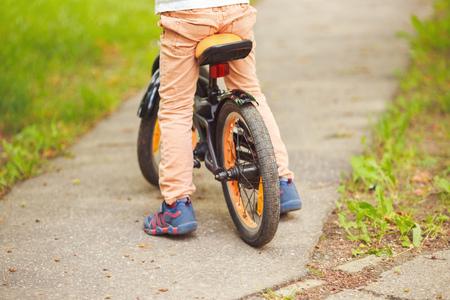 leds: Chico con una bicicleta en la calle. rueda de una bicicleta para niños Foto de archivo