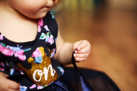 kids birthday party: little girl in a smart dress. first birthday. little girls hand