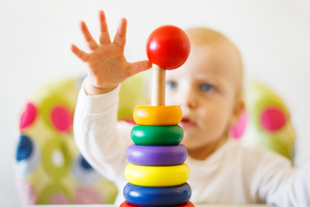 the kid plays the pyramid. child playing with wooden toys