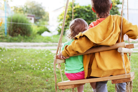 children sitting on a swing in the garden. older brother hugging little sister Banque d'images