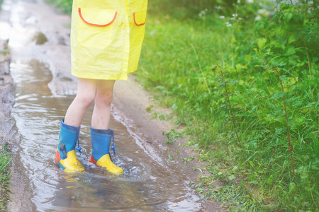 childs feet in a rubber boot in a puddle