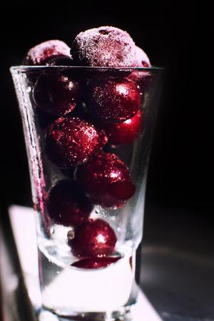 frozen cherry  close in a glass on a dark background Foto de archivo