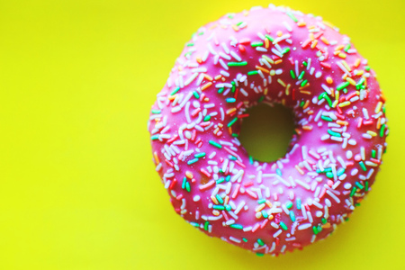 pink donut on a yellow background close