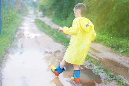 child in rubber boots playing in a puddle