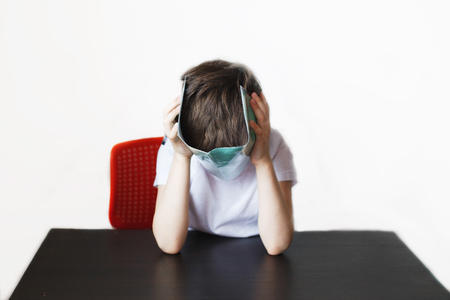the boy is tired of doing homework. the child covered his face with a notebook Banco de Imagens - 122622916