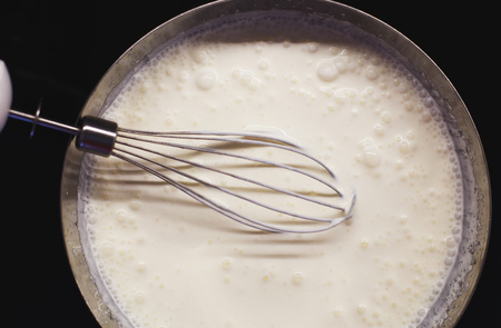 cream is whipped with a mixer in a bowl Standard-Bild