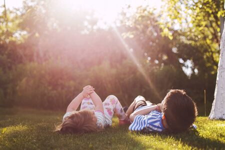 brother with  his little sister outdoor back. two children lying on the grass in the garden Stok Fotoğraf