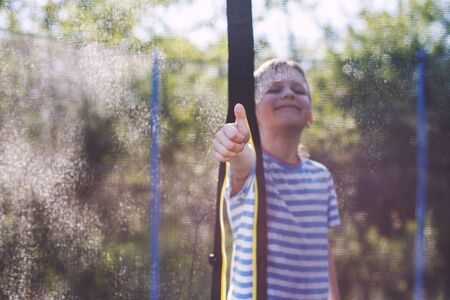 boy jumping on trampoline. child plays  and shows thumb up Stock Photo