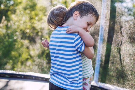 children hugging in the garden on trampoline. brother with  his little sister outdoor back