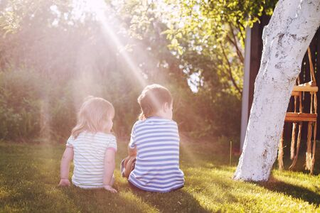 brother with  his little sister outdoor back. two children sit on the grass in the garden