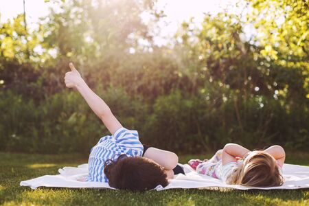 brother with  his little sister outdoor back. two children lying on the grass in the garden Stock Photo