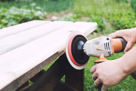 man polishes the board on the bench. man repairing bench in the garden Stock Photo