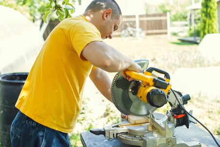 a man is cutting boards with a saw outdoor Stock Photo