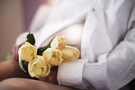 pregnant girl holding flowers. belly of a pregnant woman with flowers close