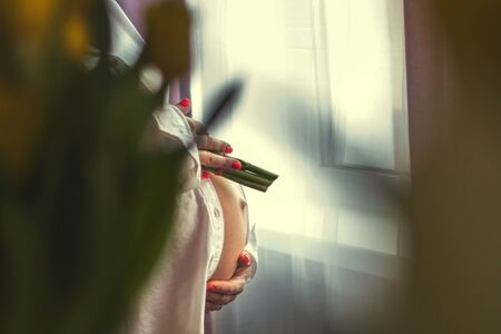 pregnant girl holding flowers. pregnant woman standing by the window with flowers. Stock Photo