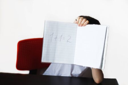the child is studying.the child decided an example . child sits and does homework on a white background