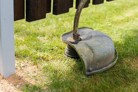 a man mows grass with a trimmer outdoor