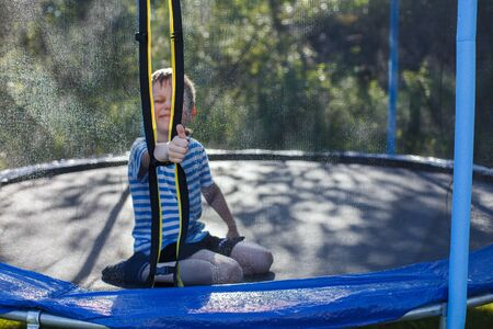 boy jumping on trampoline. child plays  and shows thumb up Banco de Imagens