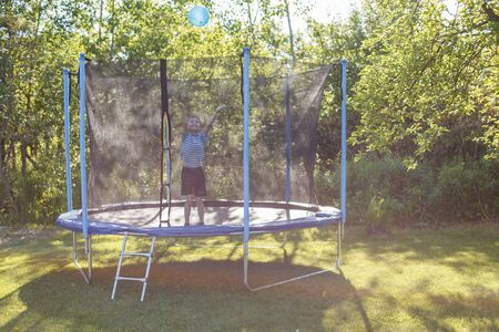 boy jumping on trampoline. child playing with a ball on a trampoline