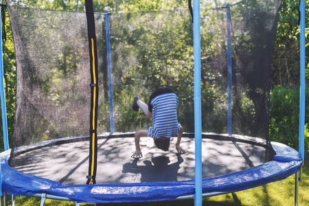 boy jumping on trampoline. a child is tumbling on a trampoline Banco de Imagens
