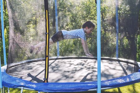 boy jumping on trampoline. the child plays on a trampoline outdoor