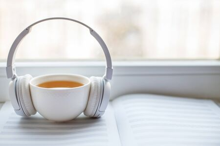 white headphones with a cup of tea on the window