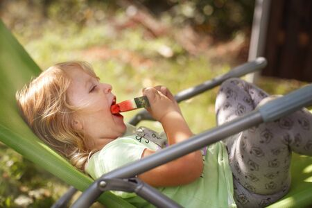 cute little girl eating watermelon on a deck chair in the garden