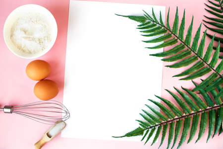 Ingredients for cooking baking - flour, egg, sugar, rolling pin on pink background. Concept of cooking dessert and sweet food.