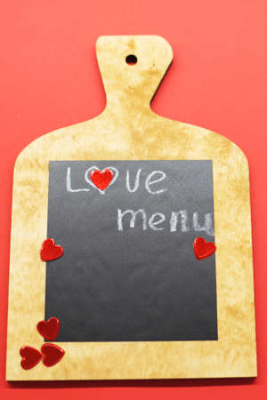 Cooking with love concept. cutting board with hearts and and the word MENU on red background