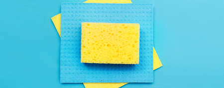 kitchen rags and sponges on a blue background. flat lay. banner.